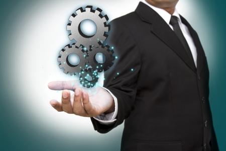 gears: Hombre de negocios que muestra engranaje para el éxito