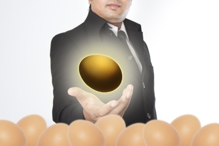 accrue: Businessman holding a golden eggs Stock Photo