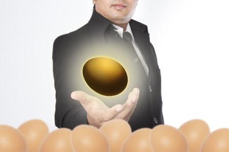 accrue: Businessman holding a golden eggs Stock Photo