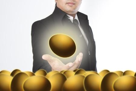 Businessman holding a golden eggs Stock Photo