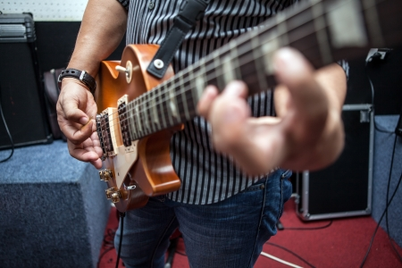 Man playing guitar in rehearsal room