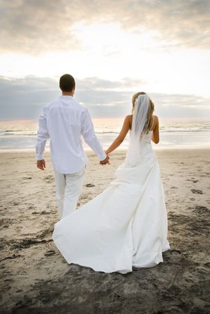 A newlywed couple taking a romantic wlak down the beach. Фото со стока