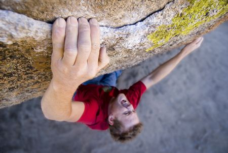 bouldering: A rock climber executing a very strenuous move.