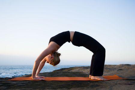 arching: Una mujer haciendo yoga por el oc�ano.  Foto de archivo