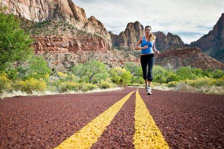 mountainous: A woman running down a mountainous road.