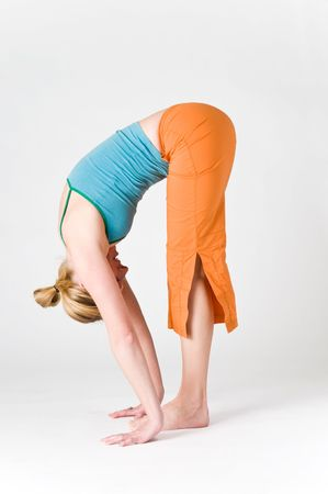 A women doing yoga with a white background.