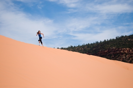 A female athlete running up a sand dune.