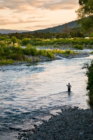 A fly fisherman casting on the Tongariro River of New Zealand. Reklamní fotografie