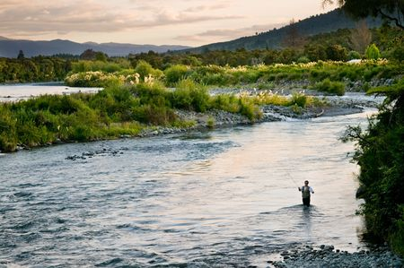A fly fisherman casting on the Tongariro River of New Zealand. Фото со стока