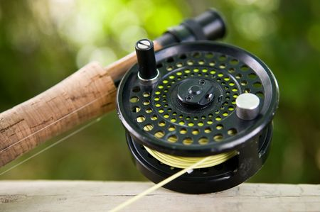 A fly reel and rod in a river setting. Reklamní fotografie