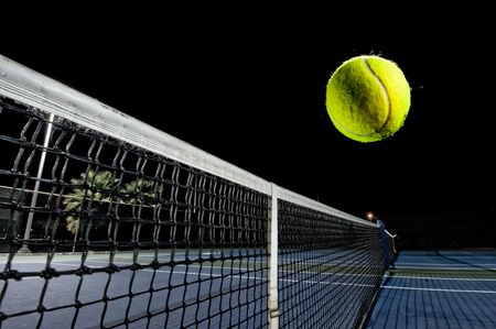 A tennis player playing at night.