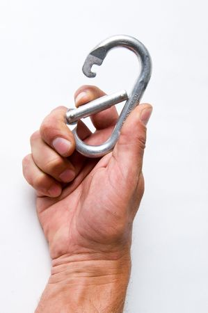 A carabiner in a climbers hand isolated on a white background. Reklamní fotografie