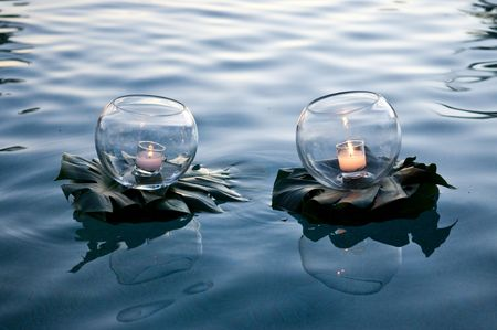 Candles on lilly pads floating in water.