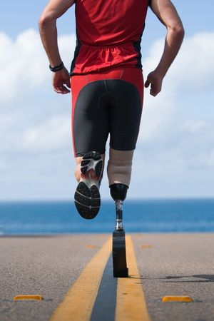 An athlete with a prosthetic leg running down the road towards the ocean. 版權商用圖片