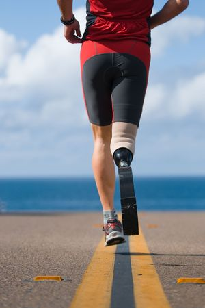prosthetic: An athlete with a prosthetic leg running down the road towards the ocean. Stock Photo