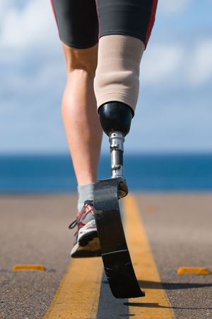 An athlete with a prosthetic leg running down the road towards the ocean. Stock Photo - 4470781