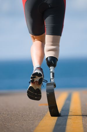 limb: An athlete with a prosthetic leg running down the road towards the ocean. Stock Photo