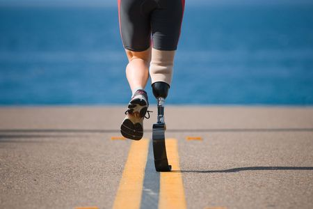 An athlete with a prosthetic leg running down the road towards the ocean. photo