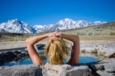 A person enjoying the mountain view soaking in a natural hot spring  in Mammoth California.  This is a very high resolution image.