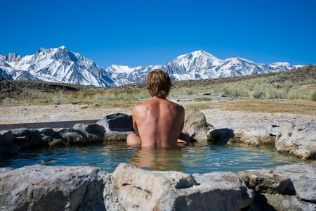 A person enjoying the mountain view soaking in a natural hot spring  in Mammoth California.  This is a very high resolution image. photo