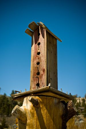 A old bird house with blue sky in the background.
