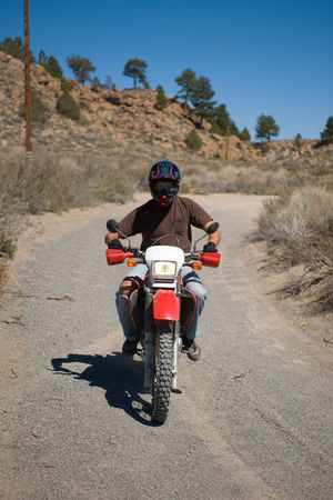 A young man riding a dirt motorcyle on a dirt road.