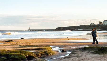 Panoramic View of Couple walking on the British Seaside at Sunset in Tynemouth, United Kingdom 02