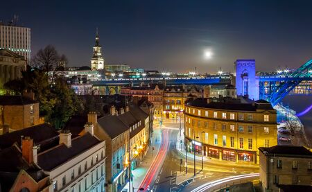 Rooftop Aerial View of British Cityscape at Night with Full Moon, Newcastle, UK Stock Photo