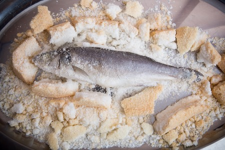 Fish baked in salt on a metal tray