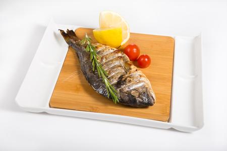 dorado fish: Whole grilled dorado fish on wooden board plate