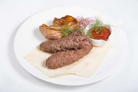 seekh: Kebab with potato garnish and tomato sauce