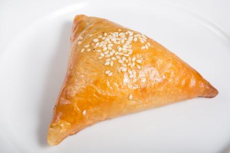 pakistani food: Fresh baked samosa with sesame seeds on white plate