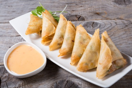 Deep fried samosas served with sauce on a wooden board Stock Photo
