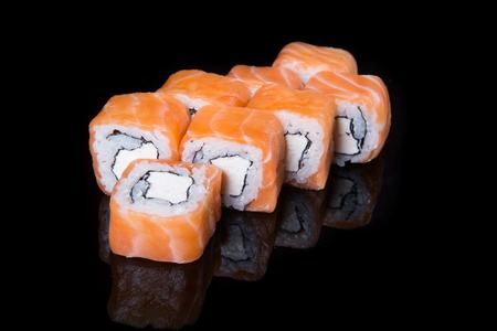 philadelphia roll: Philadelphia roll with salmon and cheese on a black background
