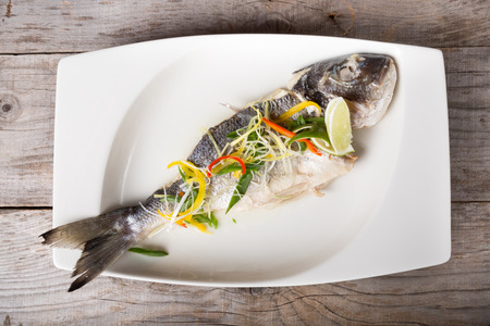 dorado fish: Cooked dorado fish served on a white plate with herbs Stock Photo