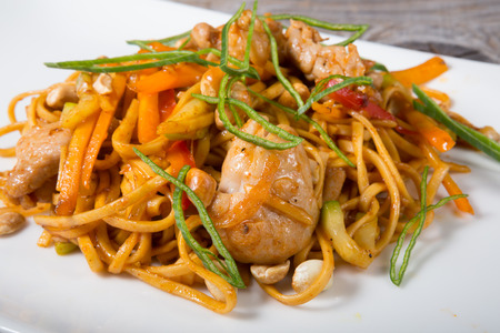 Thai fried noodles with chicken served on a white plate