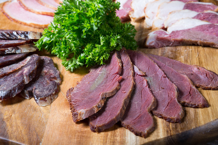 sorts: Different sorts of parma ham meat on wooden tray Stock Photo