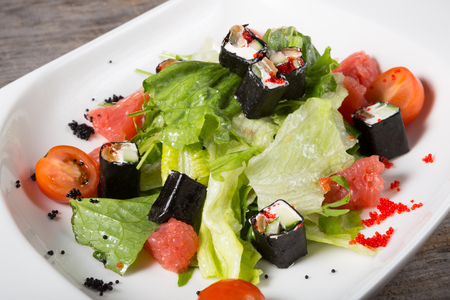 fusion: Fusion salad with grapefruits, iceberg lettuce and japanese rolls Stock Photo