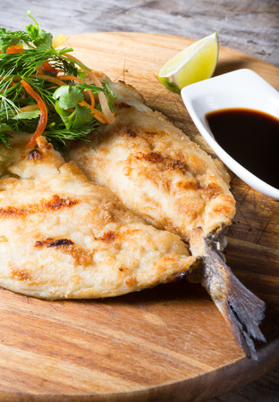 dorado fish: Fried dorado fish served with herbs and soy sauce Stock Photo
