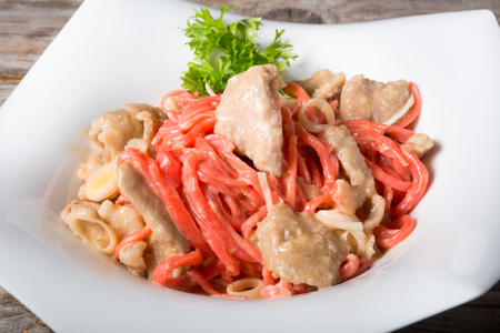 asian noodles: Red asian noodles with chicken served on a white plate