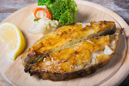 Fried white fish served on wooden board