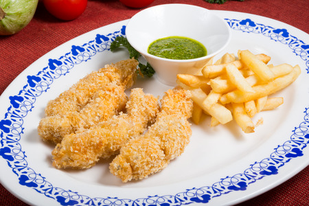 Fried pork meat with french fries and pesto sauce