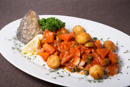 Red fish stew served on a white plate