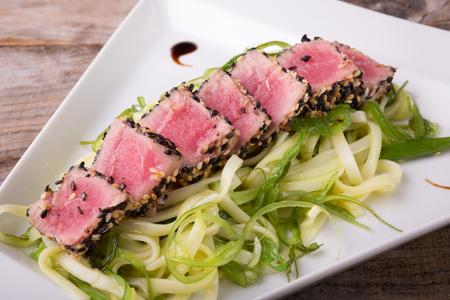 Sliced tuna meat with noodles seaweed salad