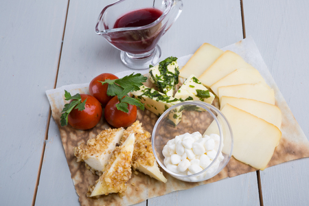 Different sorts of cheese with red cranberriy sauce