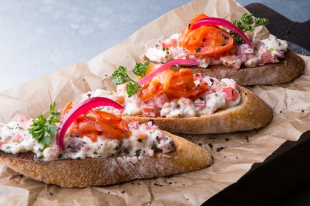 Bruschetta italian snack sandwiches with salad on wooden board