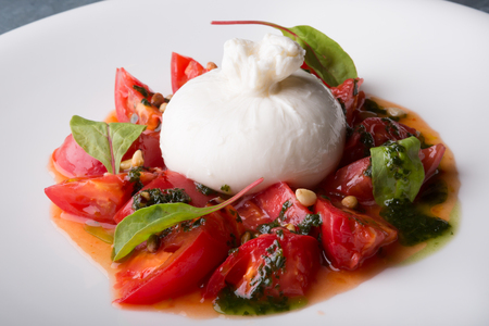 Burrata italian cheese snack with tomeatoes served on white plate Фото со стока - 90189681