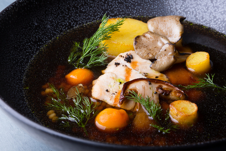 Mushroom soup with chicken and potatoes served on a black plate