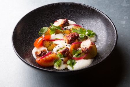 Italian cooked squid salad served in a black bowl