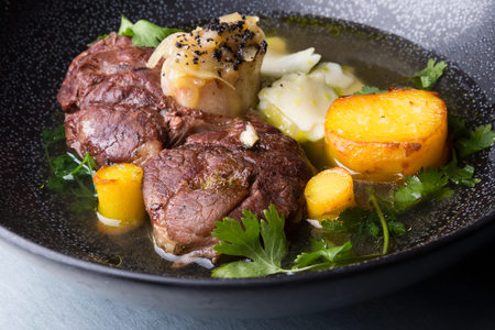 Osso buco traditional italian meat dish served on black bowl